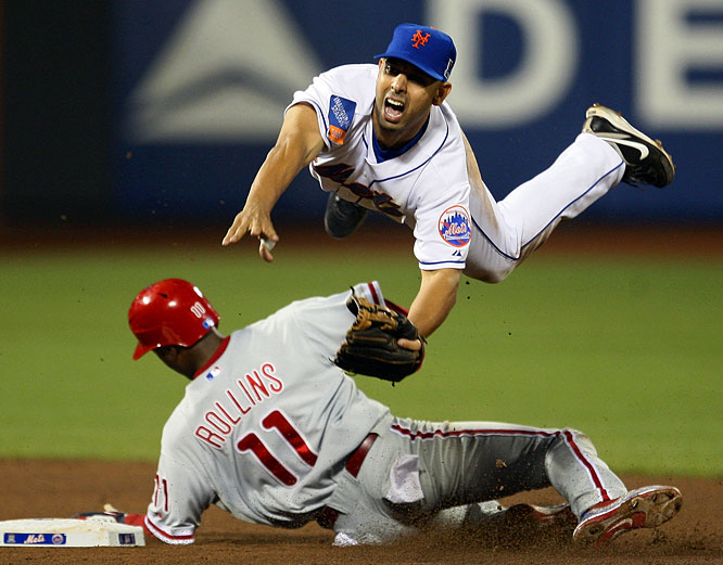 Alex Cora of the New York Mets avoids a sliding Jimmy Rollins while trying to turn two after a Ryan Howard grounder in the eighth inning. Howard was safe at first on the play, but the Mets went on to beat the Phillies 6-5 in a game that featured seven home runs.