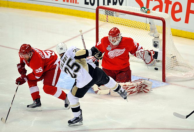 Pittsburgh's Maxime Talbot (25) puts the puck past Detroit defender Niklas Kronwell (55) and goalie Chris Osgood (30) in the second period to give the Penguins the lead at Joe Louis Arena.  Talbot scored both goals against the Red Wings in Game 7, securing a 2-1 win and the Penguins' first cup since 1992.
