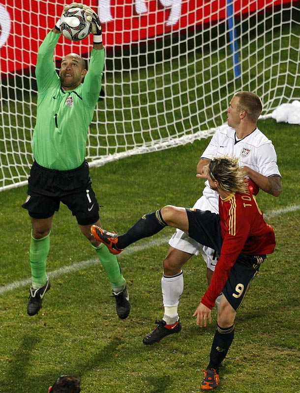 Tim Howard makes a save as teammate Jay DeMerit and Spain's Fernando Torres look on.