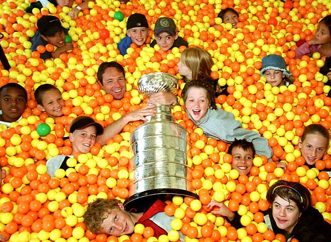 Colorado assistant GM Brian MacDonald (arms around cup), who watched his Avalanche win the 2001 title, joins children from the Memorial Boys and Girls Club in the ball room during a visit with the Stanley Cup in London, Ontario.