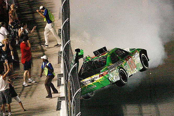 Fans escape a fiery crash as Kyle Busch hits the wall at Daytona.