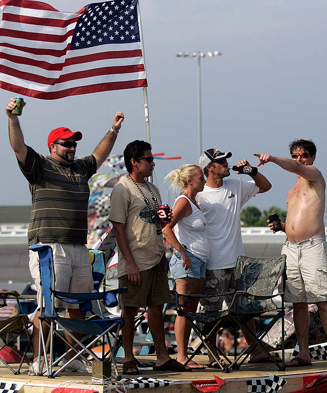 Fans gather on top of makeshift platform on a truck bed waiting for the start of the NASCAR Coke Zero 400.