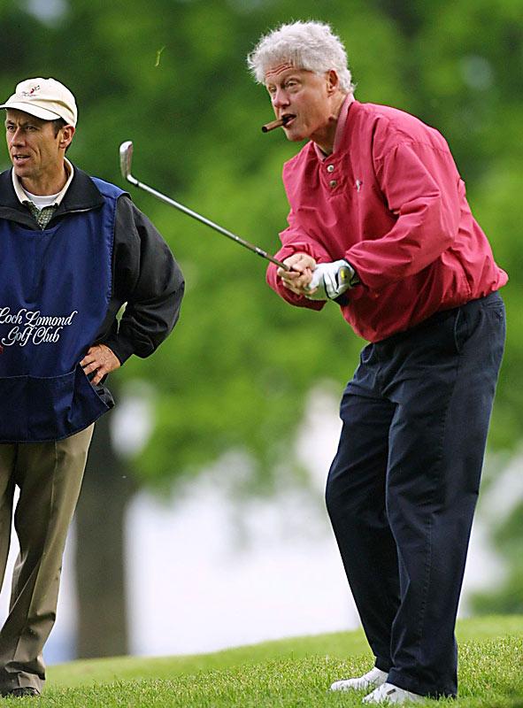 Bill Clinton enjoys a cigar while shooting a round at Loch Lomond Golf Club in Scotland.