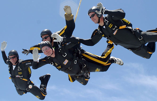 George H.W. Bush (lower center) celebrates his 80th birthday by parachuting in a tandem jump.