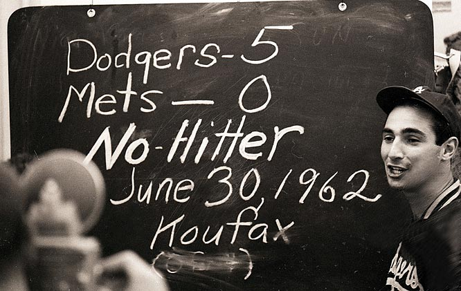 Sandy Koufax in locker room with chalkboard showing stats on his no-hitter against the Mets.