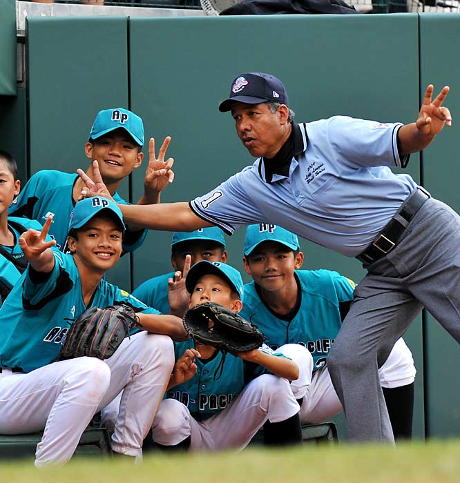 An umpire pauses for a little fun with some of the Taiwanese players during the International final.