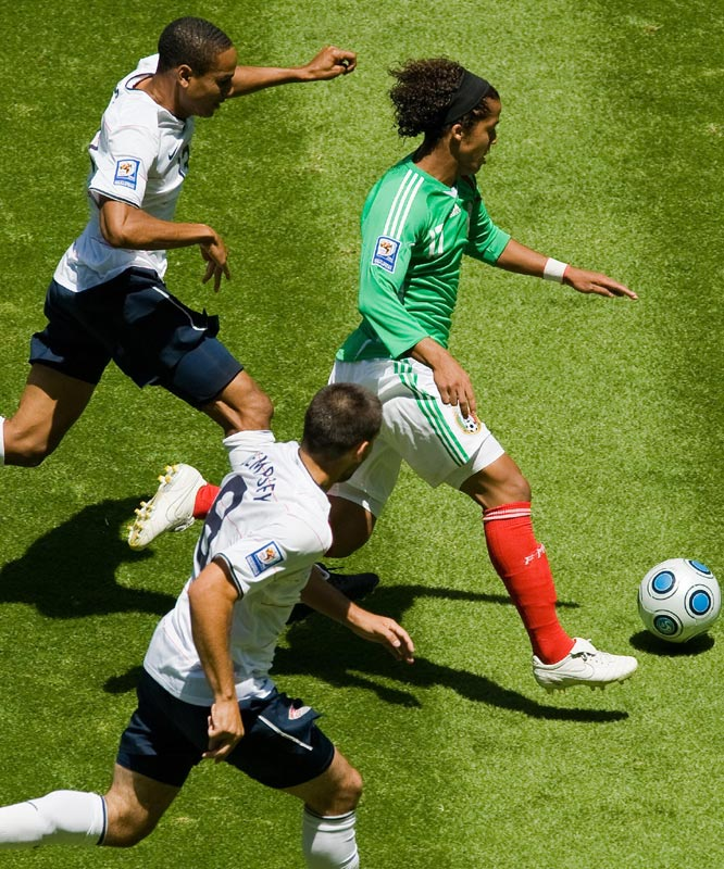 Mexico's Giovani Dos Santos (right) outruns U.S. players (from top) Ricardo Clark and Clint Dempsey to the ball.