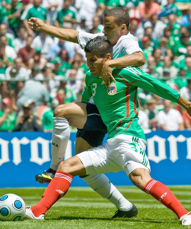 Mexico's Ricardo Magallon (front) holds off Team USA's Charles Davies while trying to control the ball.
