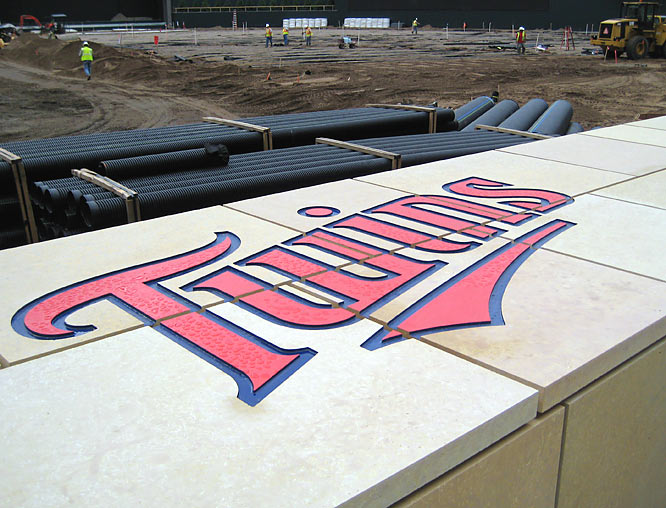 The Twins logo is etched onto limestone atop the home dugout on the first base side.