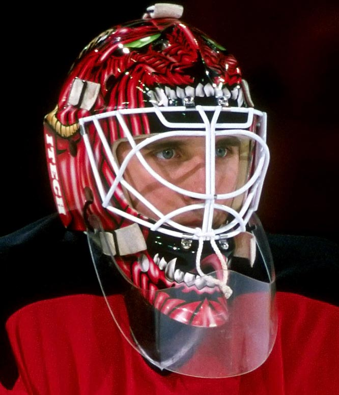 "By the 1990s, the modern goalie mask took full form with wild airbrush paint jobs no longer the exception, but the norm.  Here we rank the top 10 masks of the '90s.  Dunham's mask was a bit of a departure from the team's friendly mascot, ""NJ Devil"", as well as starter Martin Brodeur's bland mask.  Green eyes, jagged teeth, horns and a lashing tongue must have frightened plenty of young fans, and probably a few players too."