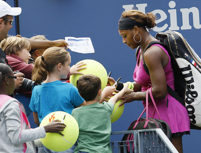 Serena Williams of the U.S. autographs tennis balls for fans after her match against countrywoman Alexa Glatch.