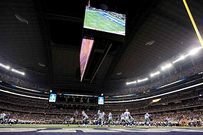 Romo drops back to pass as the video screen displays the action.