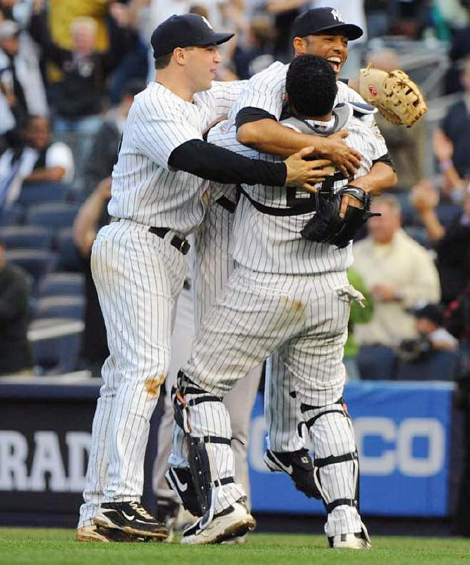 Mariano Rivera celebrated with teammates Jose Molina (right) and Mark Teixeira (left) after securing the save. The Yankees won the game 4-2 to earn their 100th win of the season and clinch the American League East.