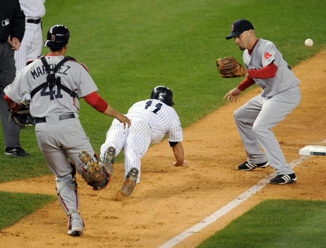 Brett Gardner dove safely back to third base as catcher Victor Martinez's throw got by Red Sox shortstop Chris Woodward, right, during the eighth inning. Gardner eventually scored on a Johnny Damon single.