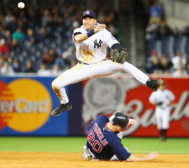The Yankees' Derek Jeter (L) turns a double play over the Red Sox's Kevin Youkilis (R) during the seventh inning of the game between the Boston Red Sox and the New York Yankees at Yankee Stadium in the Bronx, New York on 25 September 2009. The Yankees won, 9-5.