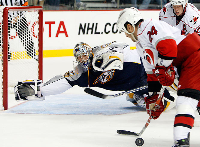 Nashville Predators goalie Pekka Rinne, of Finland, stretches out as Carolina Hurricanes center Scott Walker (24) closes in during the second period of a preseason NHL hockey game in Nashville, Tenn., Saturday, Sept. 26, 2009.
