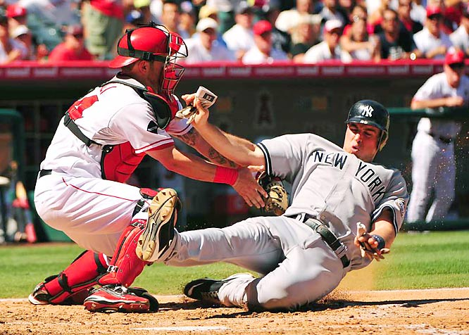 New York Yankees runner Mark Teixeira is tagged out at the plate by Angels catcher Mike Napoli after Teixeira tried to score from third base on a fly ball to left field during a game against the Los Angeles Angels of Anaheim at Angel Stadium.