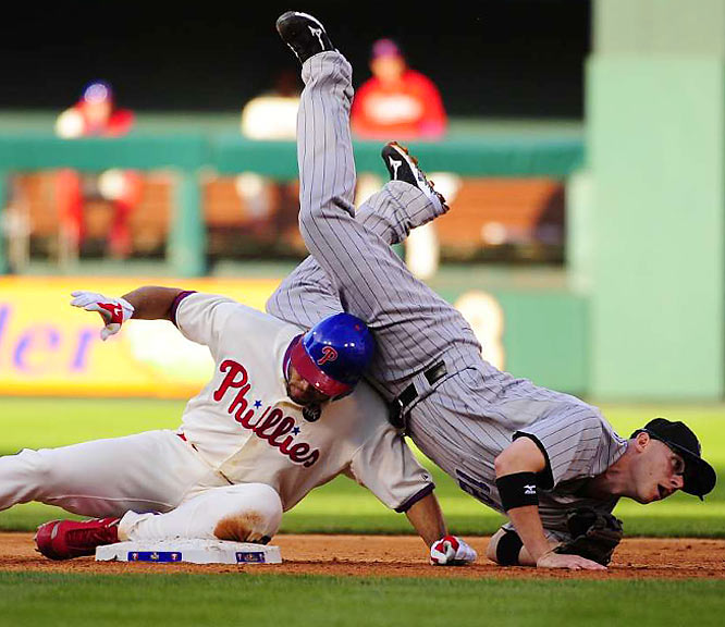 Second baseman Clint Barmes flips over Pedro Feliz after turning a double play to end the sixth inning.