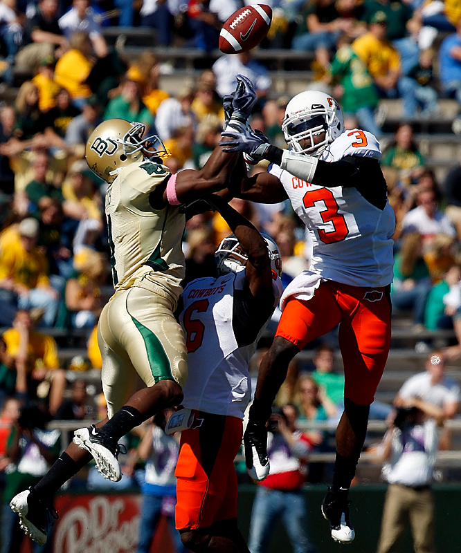 Baylor wide receiver David Gettis (left) and Oklahoma State's Victor Johnson (right) each have a leg up as they battle for the ball with Cowboy Andrew McGee during their Big 12 tussle in Waco, Texas. Zac Robinson completed 23 of 27 passes for 250 yards with a season-high three touchdowns and the Cowboys (6-1, 3-0 Big 12) stretched their winning streak to five games -- the last four without their top runner (Kendall Hunter) and top receiver (Dez Bryant) from a year ago.