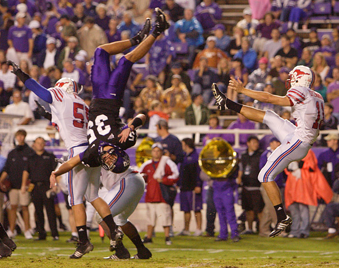 Tanner Brock (35) of TCU gets flipped in a futile attempt to block a punt by Matt Szymanski of SMU.
