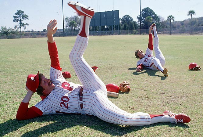 Mike Schmidt and Jay Johnstone stretch before a spring training session.