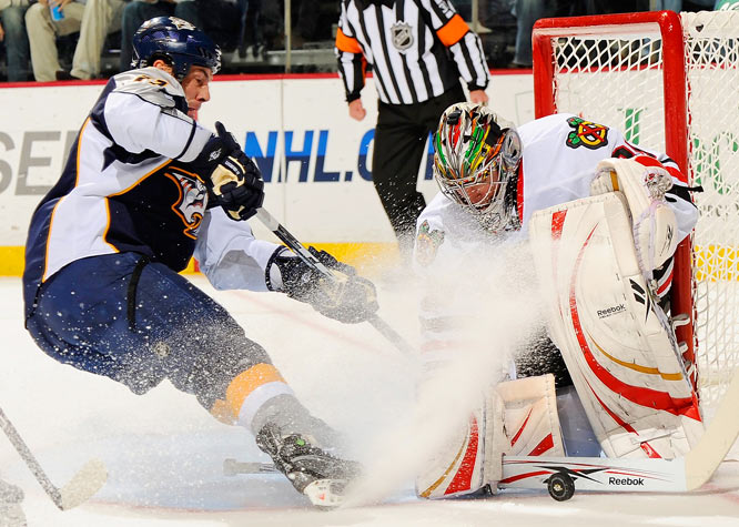 Chicago Blackhawks goalie Cristobal Huet stops the puck as Nashville Predators center David Legwand sprays him with ice during their game at the Sommet Center in Nashville. The Blackhawks defeated the Predators 3-1.