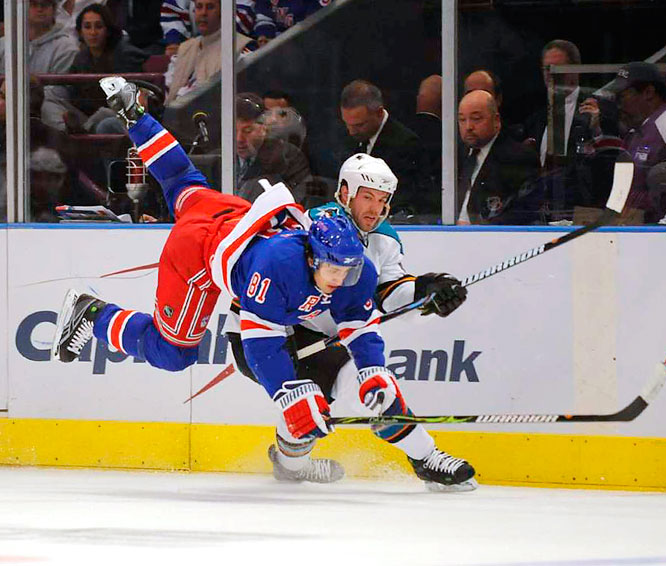 New York Rangers winger Enver Lisin is hip-checked by San Jose Sharks defenseman Kent Huskins in the first period of their game at Madison Square Garden on Oct. 19. The sharks defeated the Rangers 7-3.