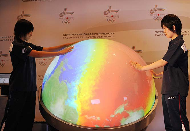 Japanese table tennis players Yu Miyahara and Ayuka Tanioka touch a globe during a press conference in Copenhagen.