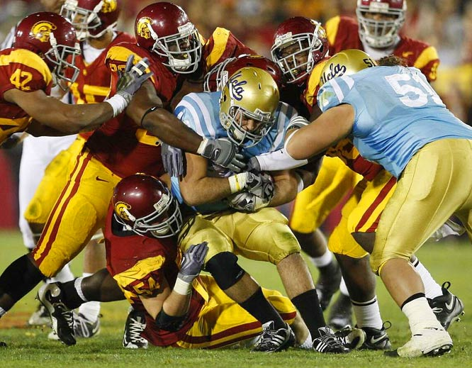 Chris Galippo, Malcolm Smith and Jeff Miller of USC  tackle Chane Moline during a 28-7 victory over crosstown rival UCLA on Nov. 28.
