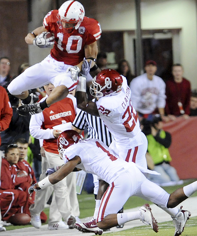 Roy Helu (left) goes vertical for extra yardage. He did plenty while on the ground, too -- finishing with 138 yards on 20 carries. Matt O'Hanlon had three of Nebraska's five interceptions against Landry Jones and the Cornhuskers squeezed enough production out of their struggling offense to upset Oklahoma.