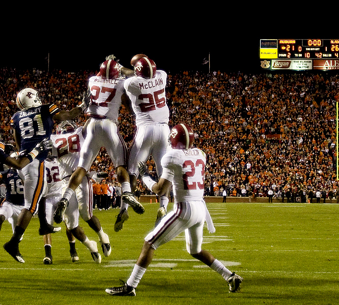 Alabama needed Justin Woodall (27) and Rolando McClain (25) to break up this Hail Mary to complete a second straight perfect regular season in the Iron Bowl. Alabama did it the hard way Friday, falling behind 14-0 in the first quarter, but ultimately did its part to set up a 1 vs. 2 showdown with top-ranked Florida in the SEC championship game. Greg McElroy 's 4-yard touchdown pass to Roy Upchurch with 1:24 left proved decisive.