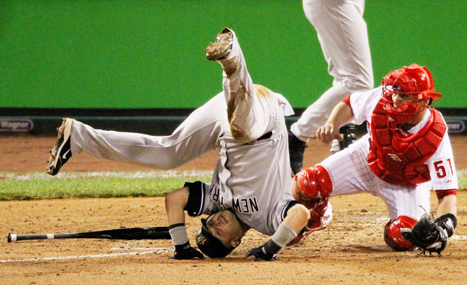 After sliding in ahead of a tag by Carlos Ruiz, Nick Swisher takes a tumble following a push by the catcher during Game 3 of the World Series.