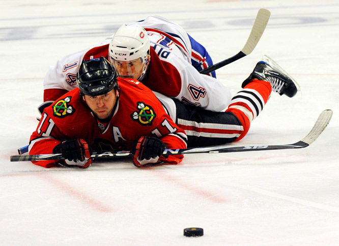 Montreal center Tomas Plekanec falls on Chicago's John Madden in the first period of their game in Chicago on Oct. 30. The Blackhawks defeated the Canadiens 3-2.