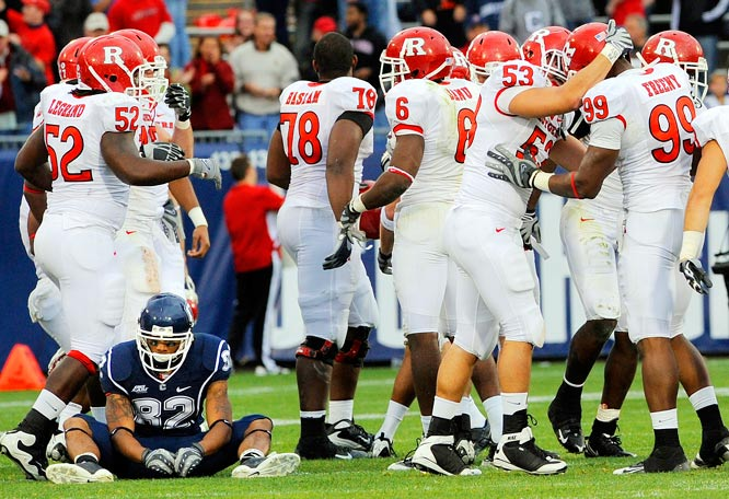 Connecticut's Kashif Moore sits in disbelief as Rutgers players celebrate their dramatic 28-24 win on Oct. 31. Rutgers quarterback Tom Savage connected with receiver Tim Brown for an 81-yard touchdown pass with 22 seconds left at Rentschler Field.