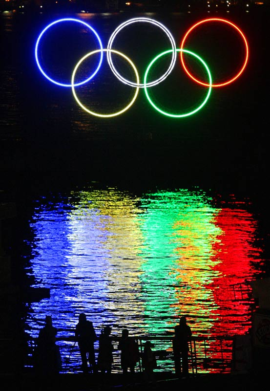 People stop to look at a  tall set of Olympic rings that were illuminated in the harbor outside the Vancouver Convention Centre in Vancouver on Nov.  4.<br><br>Send comments to siwriters@simail.com.