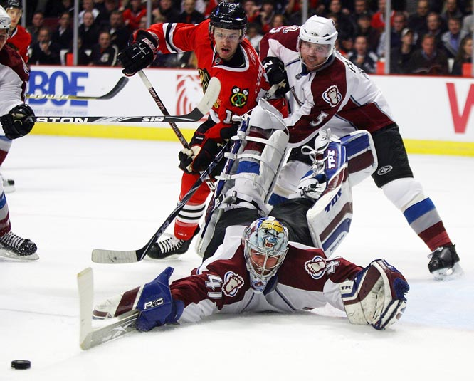 Craig Anderson of the Colorado Avalanche sprawls to make a save as teammate Brett Clark battles with Andrew Ebbett of the Chicago Blackhawks at the United Center on Nov. 11 in Chicago.