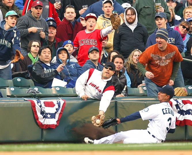 "A fan at Seattle's Safeco Field had a moment of glory but did the home team no favor by catching a foul ball before leftfielder Ronny Cedeño, could put his glove on April 14.<br><br>""Baseball engages us in ways no other sport can. I like this photograph because it captures a moment where the unlikely youthful dream of making a play in the big leagues comes true. How cool is that?"" -- Photographer Otto Greule Jr./Getty Images"