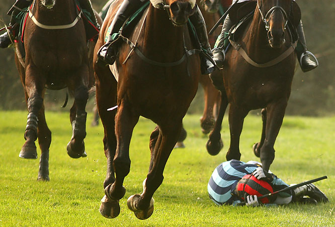 "Jockey Marcus Foley fell off his horse, Boomshakalaka, at a jump during the John Smith's Topham Steeplechase on April 3 in Liverpool, England. Foley, 28, was not injured, but retired  four months later.<br><br>""The image sums up how physical this sport can be, and to see a rider on the floor unprotected from these huge beasts passing by shows the jockeys' courage and dedication.""  -- Photographer Warren Little/Getty Images"