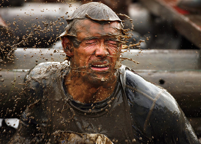 """This image from the Tough Guy Competition is my personal favorite. I just love the way the water and mud is moving around his face as he emerges from the muddy waters."""