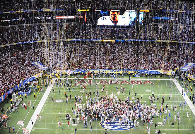 Alabama players celebrate their victory as a dejected Tim Tebow is displayed on the jumbotron.