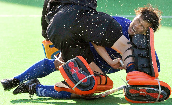 Jin Kyung-Min of South Korea collides with goalkeeper Jaap Stockmann of the Netherlands during their Champions Trophy field hockey match played in Melbourne on Dec. 1. South Korea won 2-1.