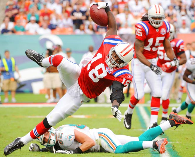 Matthew Slater of the New England Patriots is knocked off his feet by Brian Hartline of Miami on a kickoff return during the Dolphins 22-21 upset win at Land Shark Stadium in Florida on Dec. 6.