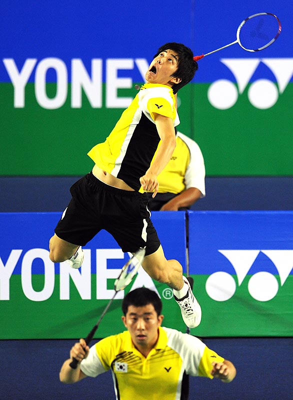 South Korea's Lee Yong-Dae jumps high above teammate Jung Jae-Sung to smash a return in the doubles final at the Badminton World Super Series Masters event in Malaysia on Dec. 6. The South Koreans won the match and took the title.