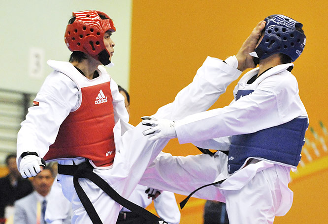 Erdenebaatar Naranchimeg of Mongolia receives a kick to the face from Chen Jiande of China during the 62-67 kg men's taekwondo semifinals at the East Asian Games in Hong Kong on Dec. 7.