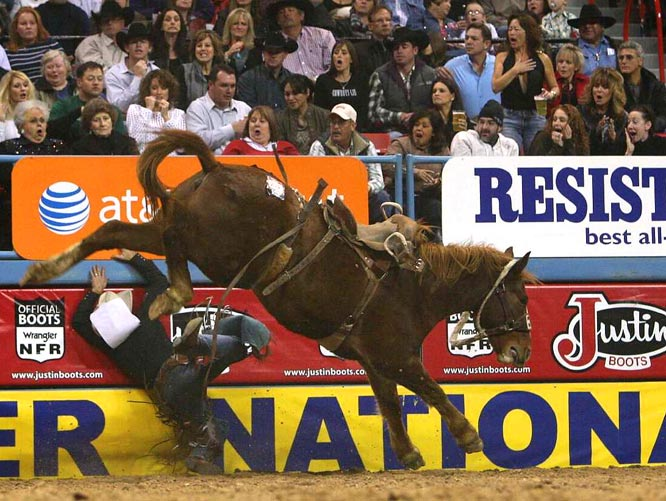 Heith DeMoss hits the fence during the 10th round of the National Finals Rodeo.