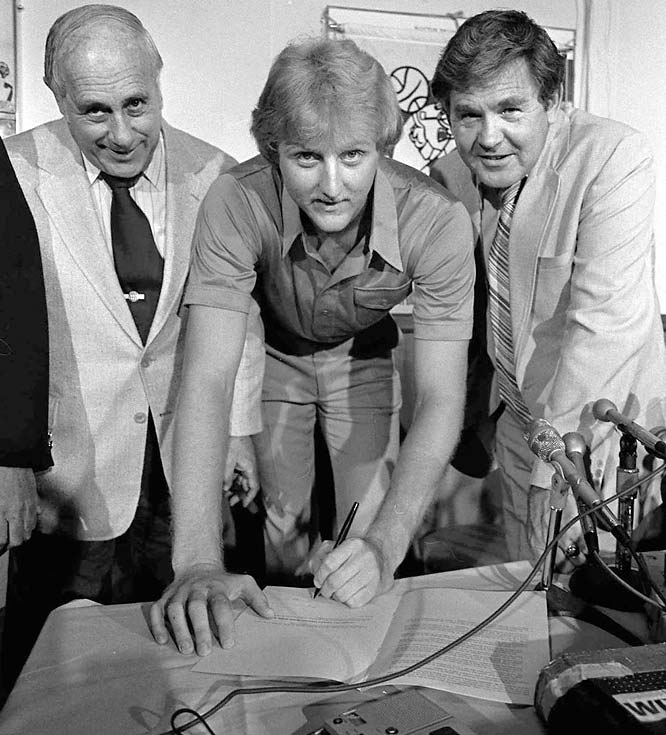 Bird became the richest rookie in sports history when he signed a five-year, $3.25 million contract in 1979. To Bird's left is Celtics President Red Auerbach and to his right is head coach Bill Fitch.