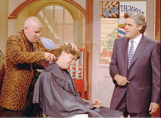 After shaving his own head following a victory in the 1995 British Open, John Daly shows off his barber skills on a member of the audience.