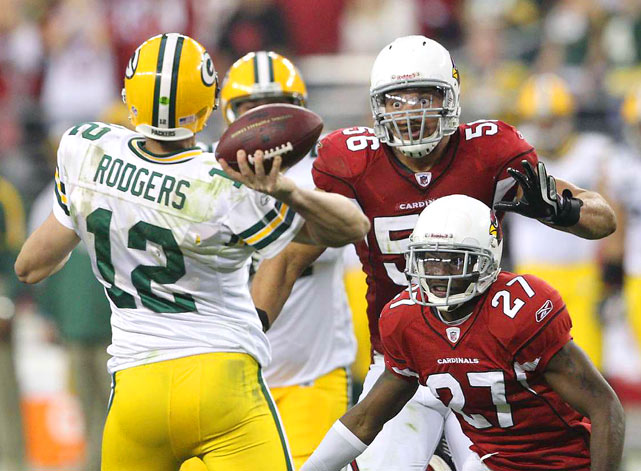 Arizona Cardinals defenders Chike Okeafor and Michael Adams eyeball Green Bay Packers quarterback Aaron Rodgers as he passes downfield during their NFC wild-card playoff matchup Jan. 10. The Cardinals defeated the Packers 51-45 in overtime.