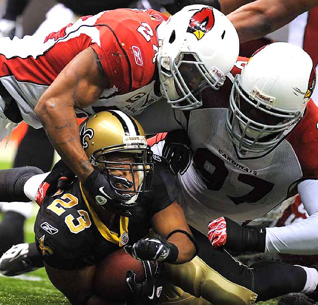 Arizona's Michael Adams (left) and Bryan Robinson (right) combine to tackle New Orleans Saints running back Pierre Thomas during the New Orleans Saints 45-14 divisional playoff win at the Louisiana Superdome on Jan. 16.