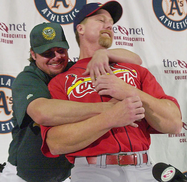 Jason Giambi gives his former teammate a bearhug during a news conference before an exhibition game between the A's and Cardinals.